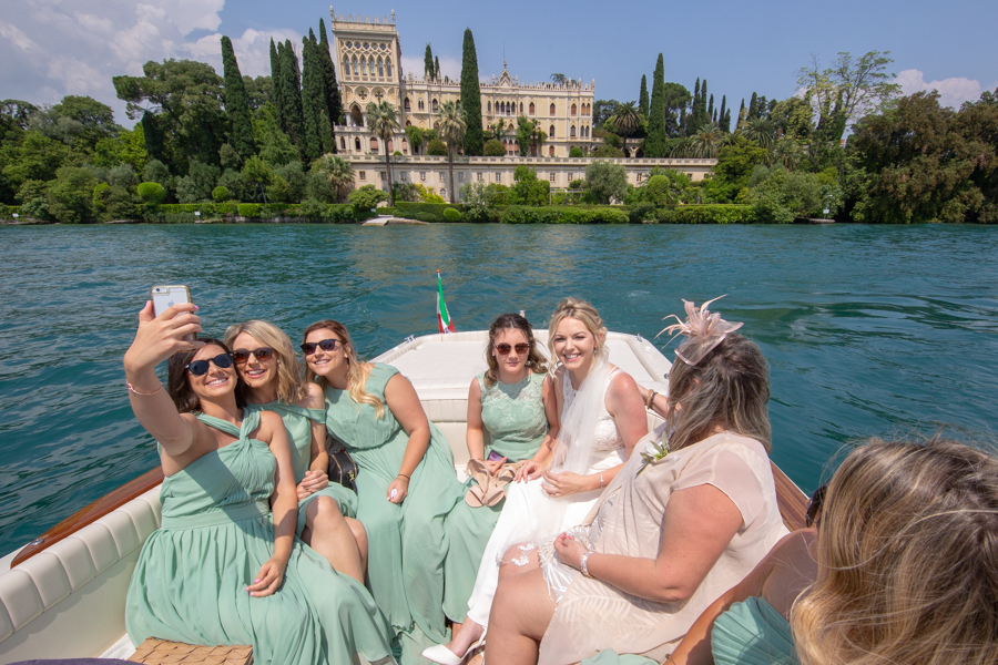 Bride and bridesmaids make a Selfie on the motorboat as they go to the island of Garda